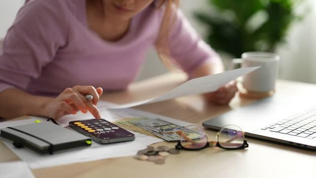 vidéos et rushes de femme de plan rapproché travaillant sur des rapports financiers - finances personnelles