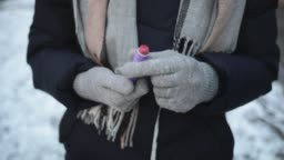 Close-up woman's hands get lipstick from pocket to apply on lips while standing on snowy street in city in winter.