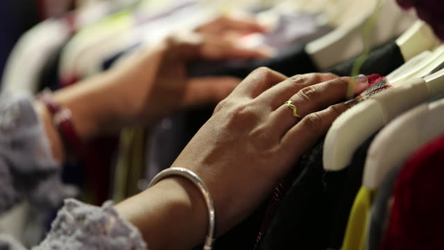 Closeup woman's hands looking through clothes rack, Slow motion