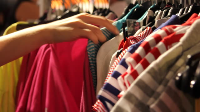 stockvideo's en b-roll-footage met closeup woman's hands looking through clothes rack - koopwaar