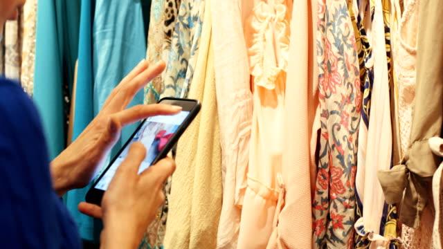vídeos de stock e filmes b-roll de closeup woman's hands looking through clothes - loja de roupa