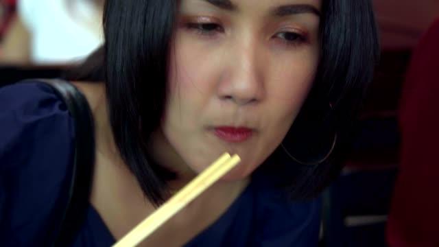 närbild ung asiatisk kvinna äta kokt chef lax fisk och söt sås (lax kabutoni) med sushi rolls och japansk mat. - varmrättssås bildbanksvideor och videomaterial från bakom kulisserna