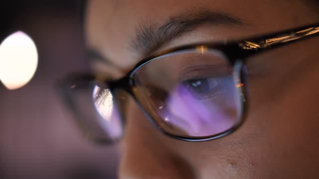 クローズアップ若いアジアの女性の目は、コンピュータ上で作業し、ラップトップのモニターを見て - desktop pc点の映像素材/bロール
