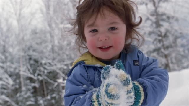 close-up young boy tasting ice and playing in snow / franconia, grafton county, new hampshire, usa - skijacke stock-videos und b-roll-filmmaterial