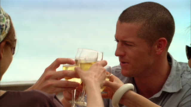 close-up young couples toasting with wine at seaside restaurant during vacation/ harbor island, bahamas - bicchiere da vino video stock e b–roll