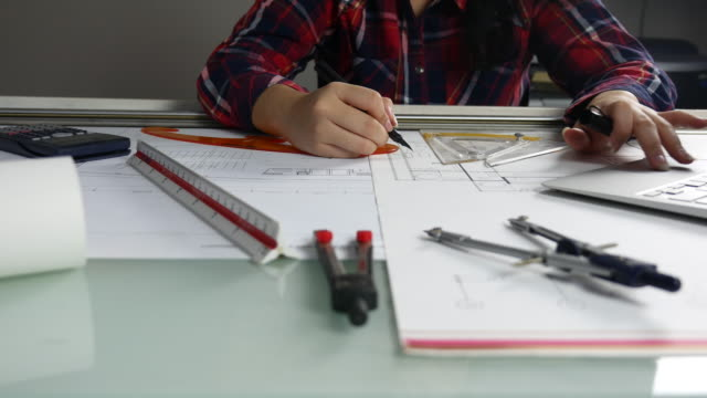 Close-up Young female architect working at desk on blueprint In Office