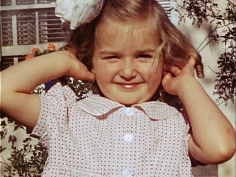 1949 close-up young girl wearing hair bow and smiling outside house / los angeles, california, usa  - hair bow stock videos & royalty-free footage