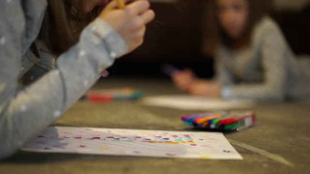 stockvideo's en b-roll-footage met closeup young girls drawing - op de buik liggen