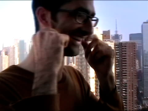 Close-up, young man standing on balcony demonstrating flexibility by pulling on the skin of his neck and face, cityscape in background/ New York City