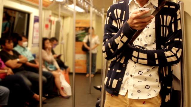 vidéos et rushes de gros plan de jeune homme à l'aide de smartphone sur le train. - tramway