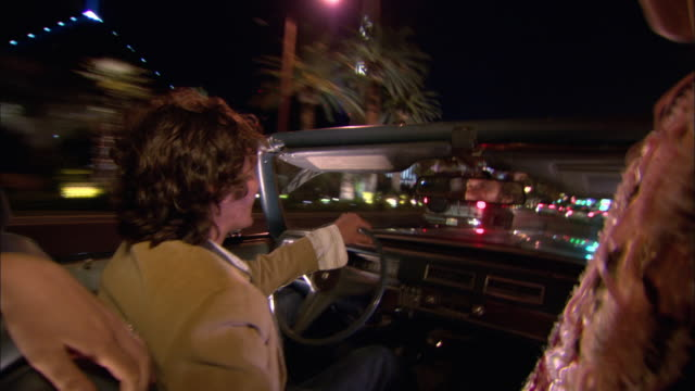 stockvideo's en b-roll-footage met close-up young men and women driving in convertible down the strip at night/ las vegas, nevada, usa - 2007