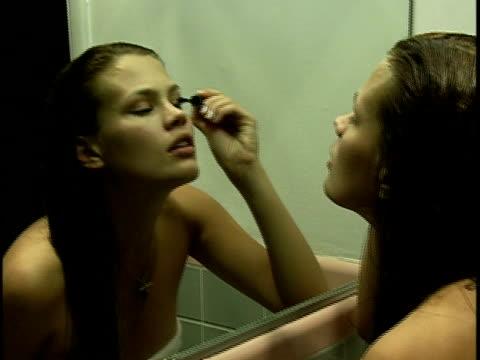vídeos de stock e filmes b-roll de close-up young woman applying mascara in bathroom mirror - só mulheres jovens