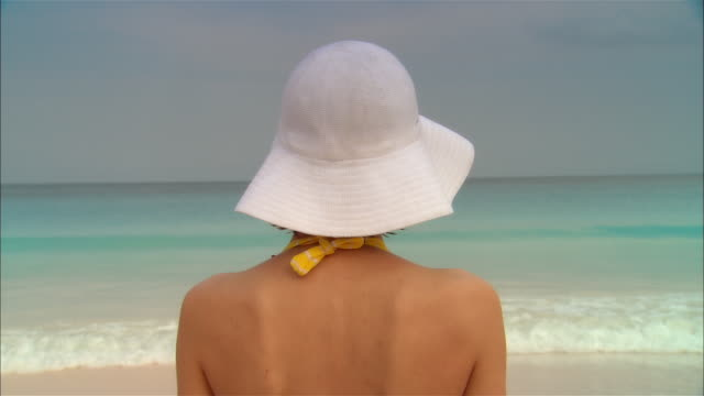 close-up young woman looking at ocean on beach/ harbor island, bahamas - bikinioberteil stock-videos und b-roll-filmmaterial