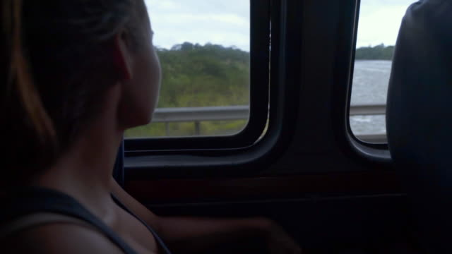 close-up: young woman looking through bus window - mittelamerika stock-videos und b-roll-filmmaterial