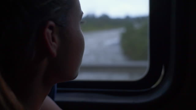 Close-up: Young Woman Looking Through Bus Window While Crossing a River