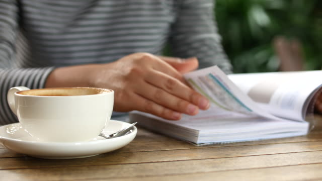 Close-up jonge vrouw lezing magazine in café, 4k (UHD), Dolly schot