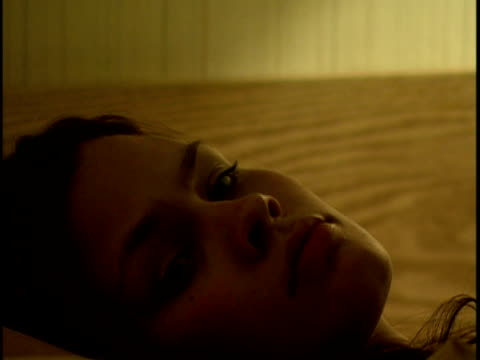 vidéos et rushes de close-up young woman staring upward and lying on bed in motel room - grognon