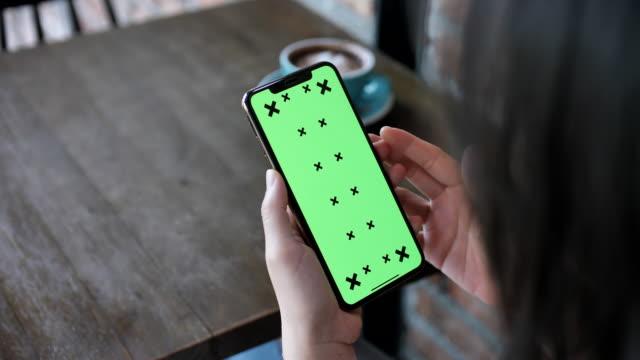 jugendliche mit ihrem grünen bildschirm-touchscreen auf dem handy im café - abspann stock-videos und b-roll-filmmaterial