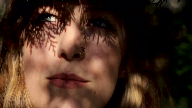 close-up young woman with beautiful face and with a nose piercing features enjoying sun - nose piercing stock videos & royalty-free footage
