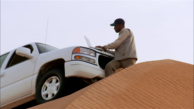 close-up zoom out man using laptop computer on hood of suv on sand dune in desert - arid stock videos & royalty-free footage