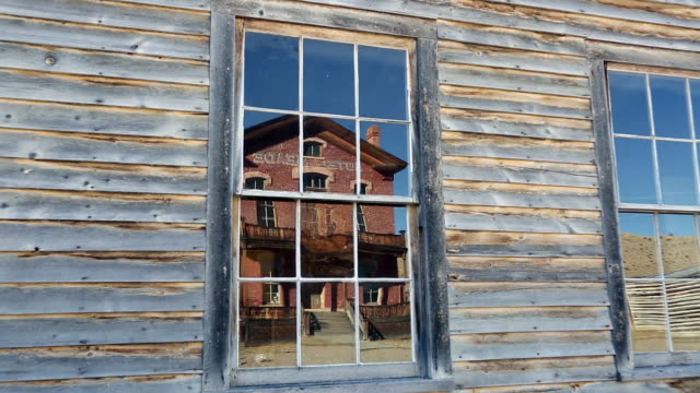 closeup zoom shot of reflection of old abandoned brick hotel in ghost town of bannack, mt in window of faded paint wall. - cottonwood tree stock videos and b-roll footage