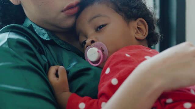 vidéos et rushes de plan rapproché, mère africaine heureuse de étreignant doucement apaisant adorable bébé nouveau-né âge 3 mois tandis qu'à lui dormant bébé dans ses bras. famille aimante heureuse. family relationship.families en afrique du sud concept. - new age concept