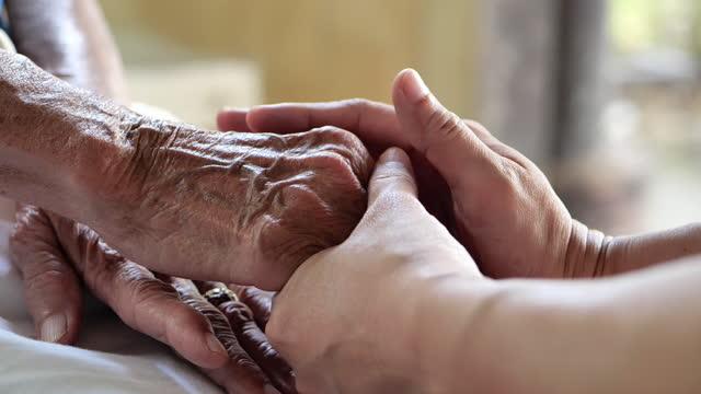 vidéos et rushes de gros plan, psychologue femme assise et touche main déprimée femmes âgées pour la visite d'encouragement à la clinique. concept moderne de santé mentale. - donner un coup de main