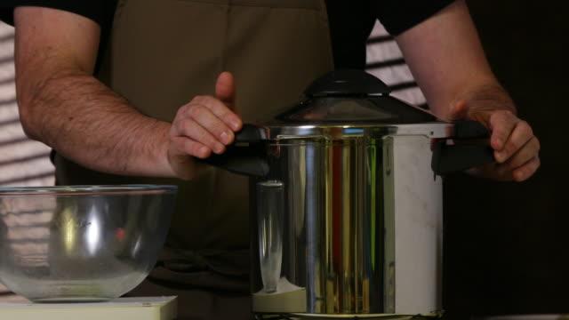 Closing lid of pressure cooker.