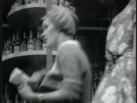 cloth goods on counter people walking by liquor store man taking bread off shelf large bread shop display canned goods liquor on display cu caviar... - 1935 stock videos & royalty-free footage