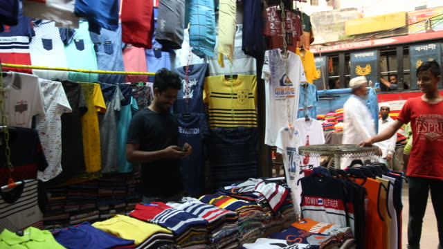 A cloth vendor sorts his goods at his booth at a street in Dhaka