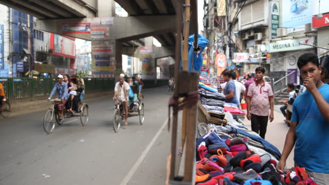 A cloth vendor sorts his goods at his booth at a street in Dhaka while as well a lot of colorful rickshaws can be seen