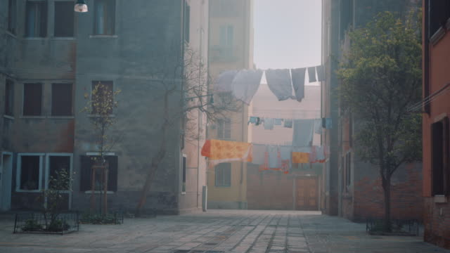 WS - Clothes and bed sheets hanging between two buildings, misty weather