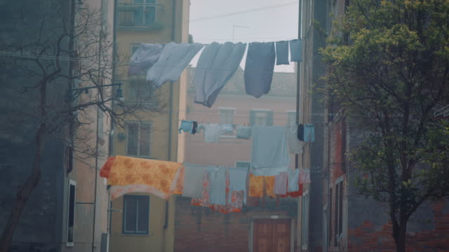 CU - Clothes and bed sheets hanging between two buildings, misty weather