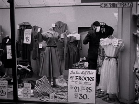 clothes and shoes are marked up with discount prices in a department stores shop window. - department store stock videos & royalty-free footage