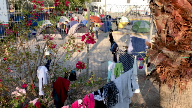 clothes are hung to dry at an immigrant camp on december 08, 2019 in the border town of matamoros, mexico. more than 1,000 central american and... - mexican american stock videos & royalty-free footage