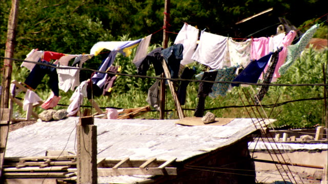 clothes dry on a line above the roof of a small shack available in hd. - buenos aires video stock e b–roll