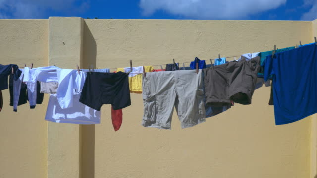 clothes drying on clothing line against blue sky - dry clothes stock videos and b-roll footage