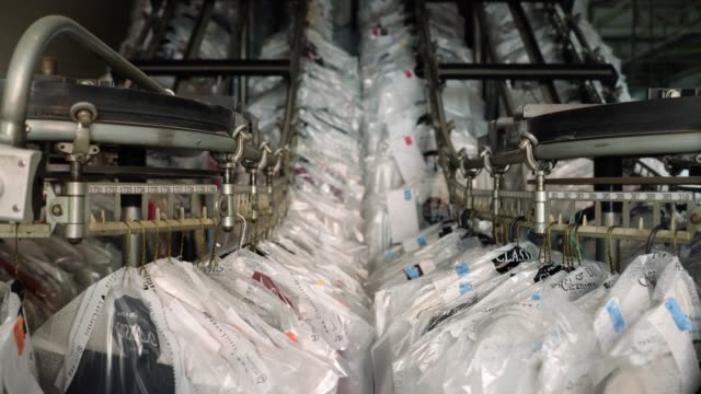 clothes hanging on conveyor belt on movement at an industrial laundry service - officina video stock e b–roll