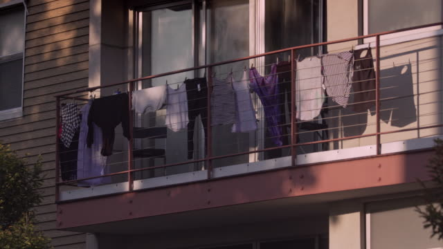 vídeos de stock e filmes b-roll de clothes hanging out to dry on apartment terrace in brooklyn, new york city. - vestido