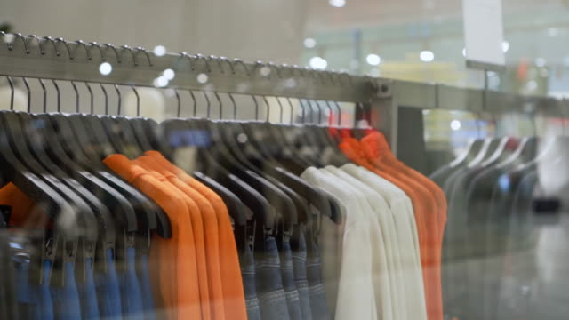 clothes hanging rail in clothes shop - clothes shop stock videos & royalty-free footage