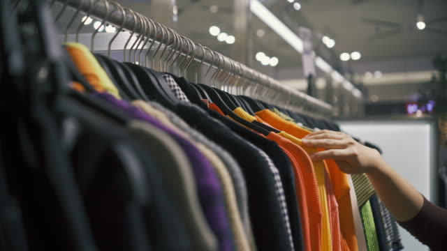 clothes hanging rail in clothes shop - coathanger stock videos & royalty-free footage