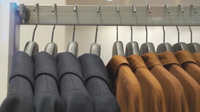 stockvideo's en b-roll-footage met kleren die spoor in klerenwinkel hangen - kledingrek