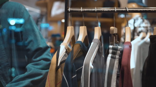 clothes hanging rail in clothes shop - department store stock videos & royalty-free footage