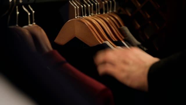 vídeos de stock e filmes b-roll de clothes hanging rail in clothes - loja de roupa