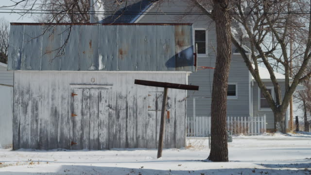 A clothes line pole stands lonely in the backyard of a small town home as the wind blows snow.
