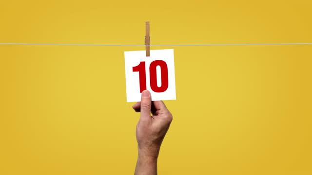 vidéos et rushes de compte à rebours corde à linge 10 à 0 sur fond jaune - chiffre 5