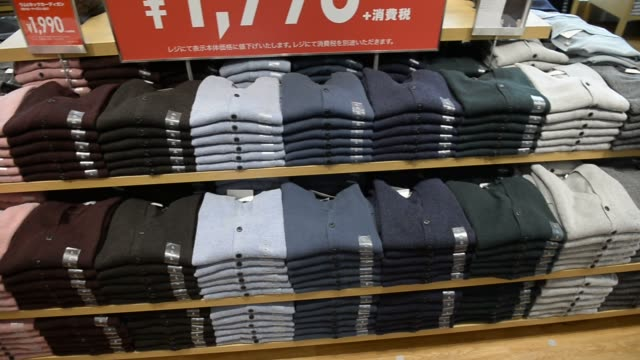 Clothing are displayed at a new Uniqlo store operated by Fast Retailing Co during a press preview in Tokyo Japan Close up shots of tags on articles...