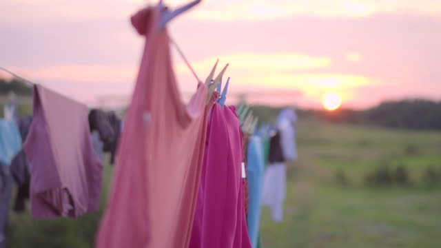 clothing drying in the wind on sunset - hanging stock videos & royalty-free footage