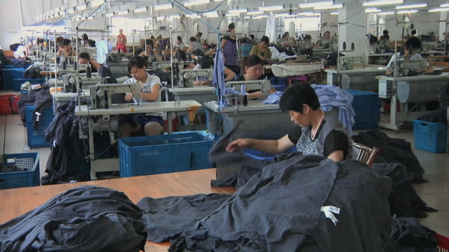 ws clothing factory floor with rows of women at sewing machines / ningbo, zhejiang, china - officina video stock e b–roll