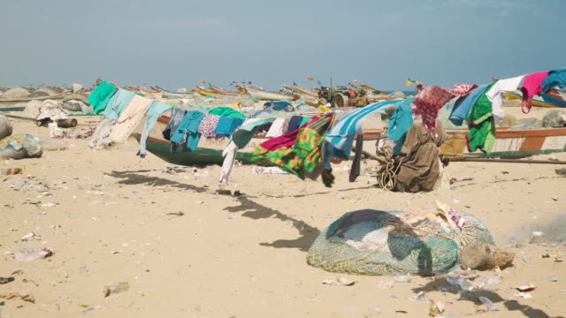 clothing hanging at beach slums of chennai india - flüchtling stock-videos und b-roll-filmmaterial